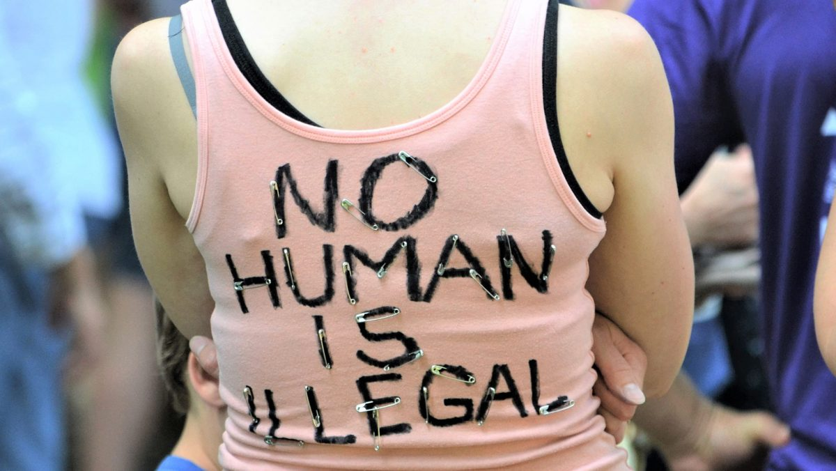 A young person wears a t-shirt reading No human is ilegal