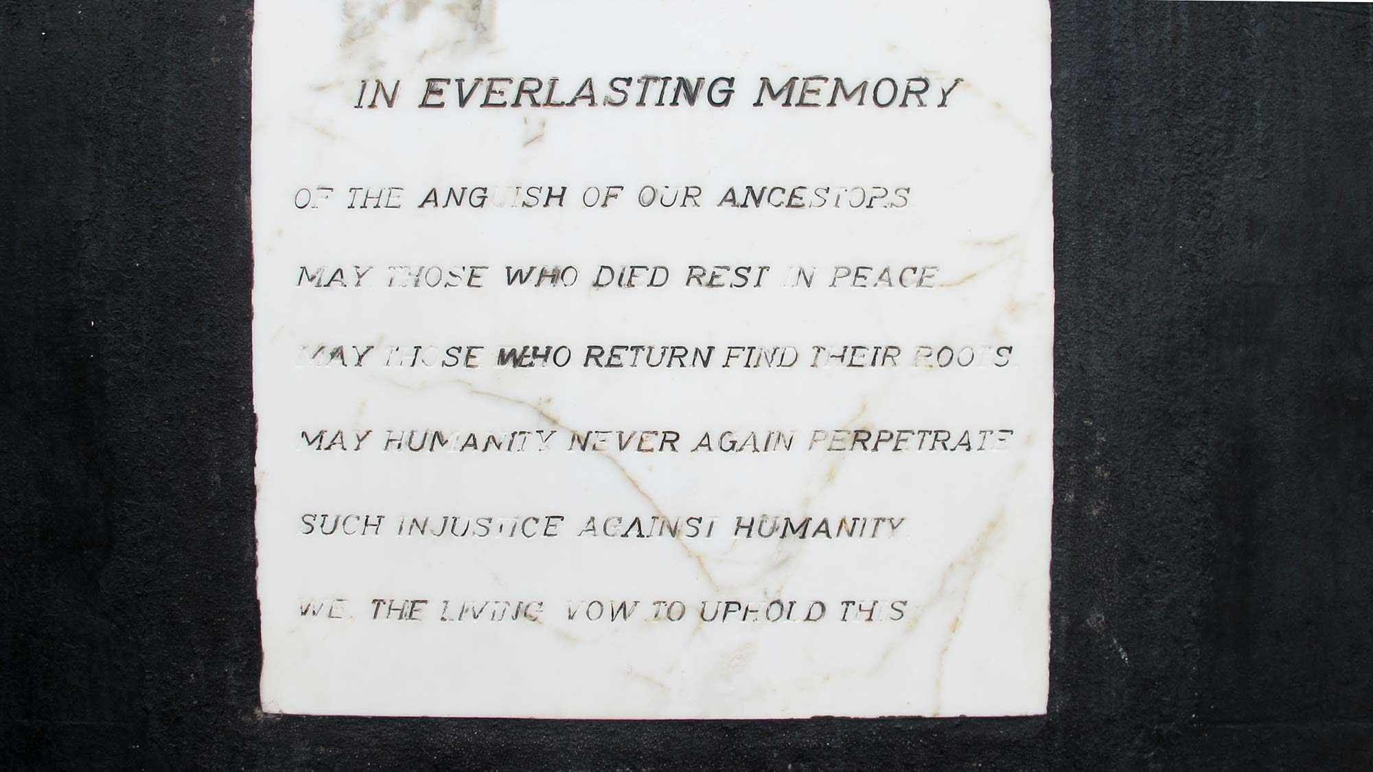 A memorial plaque reading: In Everlasting Memory of the anguish of our ancestors. May those who died rest in peace. May those who return find their roots. May humanity never again perpetrate such injustice against humanity. We the living vow to uphold this.