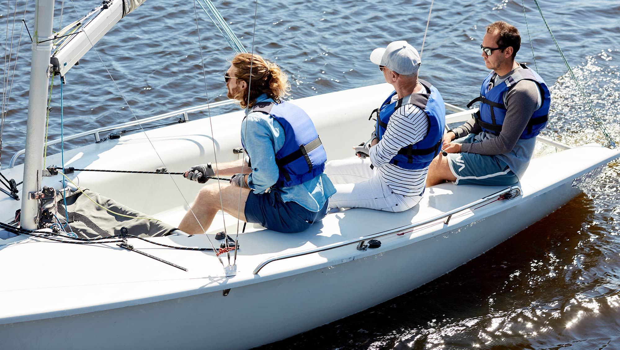 Three people sailing in keelboat